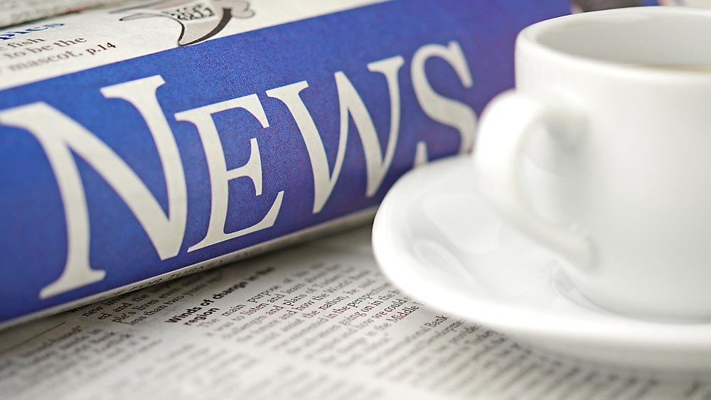 Wellspect About Rolled up newspaper and cup of coffee
