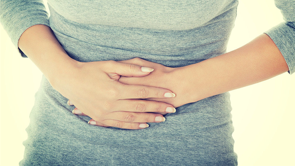 Causes of UTI woman holding her stomach in pain